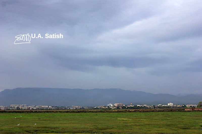 landscape; nature; outdoor; sky; clouds; overcast; buildings; birds; mountain;